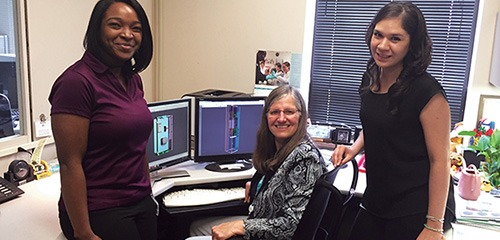 Co-op student Tamisha Banks, Jayne Beck, and engineer Yasmin Bolanos (l-r) review 3D drawings.