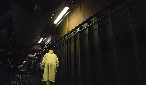 A worker wearing protective gear walks down a hallway in Building 9212. The building's aging infrastructure and equipment make obtaining replacement parts for electrical, ventilation, fire-protection, and other systems a challenge.