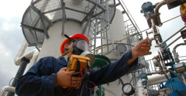The worker in a gas mask looks at a manometer of the gas refinery